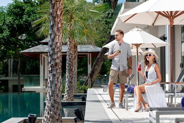Een romantisch koppel drinkt cocktails en geniet van een prachtig uitzicht op een luxe villa tussen palmbomen en een zwembad.