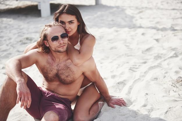 Een romantisch koppel op het strand in een zwembroek, mooie sexy jonge mensen.