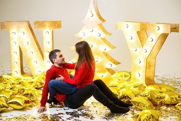 Een romantisch moment. een stel in rode truien ligt op de grond te knuffelen en te zoenen