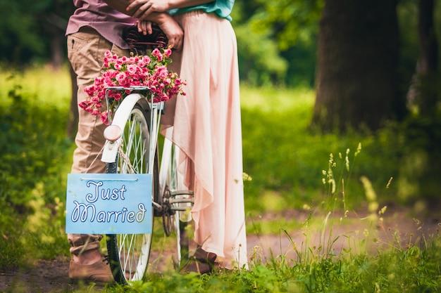 Een romantisch paar staat in de buurt van een fiets met een mand met rozen in het park