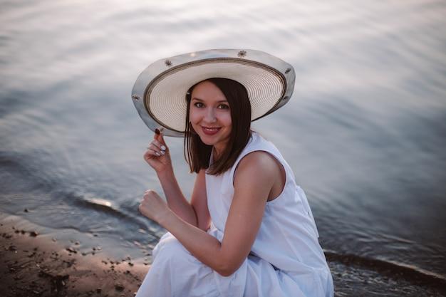 Een romantisch portret van een lachend meisje in een witte zomerjurk en een strohoed op een date op het strand door...