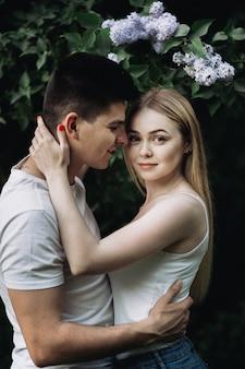 Een romantisch verliefde paar knuffelen voor een bloeiende struik