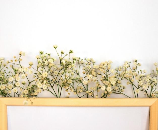 Een romantische compositie van bloemen. witte gipskruid bloemen, fotolijstjes op een witte achtergrond.