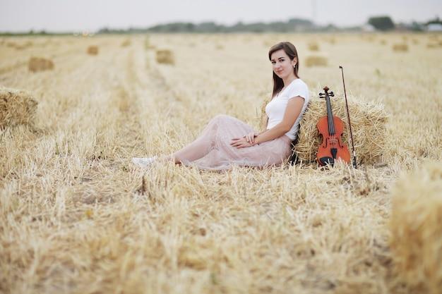 Een romantische jonge vrouw met losse haren zit in een veld naast een bundel hooi