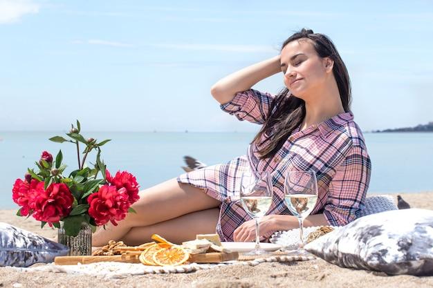 Een romantische picknick aan de zanderige kust van het strand met bloemen en glazen drankjes. het concept van zomervakantie.