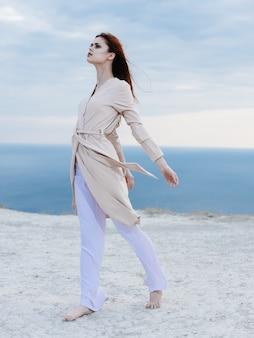 Een romantische vrouw in lichte kleren loopt over het zand en de oceaan op de achtergrond