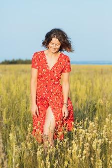 Een romantische wandeling van een meisje met krullen in een rode lange jurk langs velden. het concept van vrouwelijke vrijheid, emancipatie en liefde
