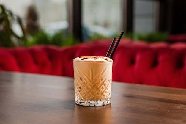 Een romige koffie-alcoholische cocktail in rotsen, lowball, ouderwets glas, gegarneerd met koffiebonen