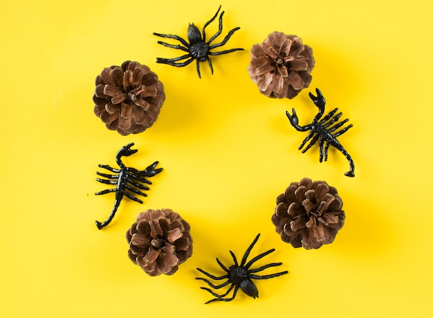 Een rond frame van kegels en figuren van spinnen en schorpioenen op een gele achtergrond halloween achtergro...