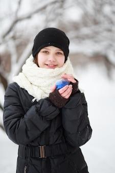 Een rond nieuwjaarsspeelgoed in de handen van een meisje. het kind maakt zich klaar voor kerstmis. om een kerstboom te versieren.