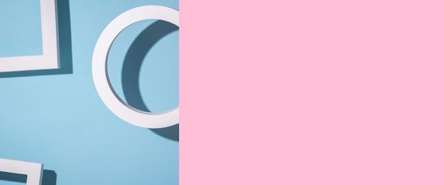 Een rond ringpodium op een blauwe achtergrond piept uit een roze kartonnen backgroundbanner.