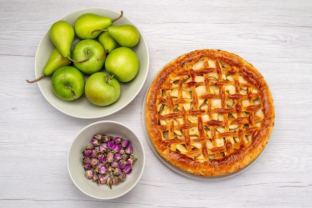 Een ronde fruitcake van bovenaanzicht heerlijk met appels en peren op de bloem van het het koekjesfruit van de lichttafelcake