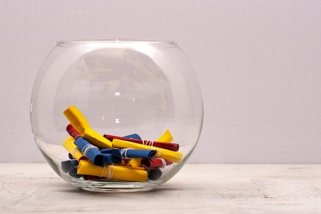 Een ronde glazen pot met gekleurde tonen van ambachtelijk papier.