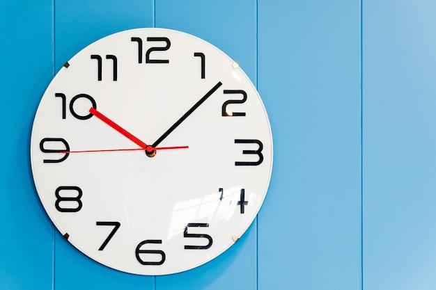 Een ronde klok die aan de muur van blauw hout hangt