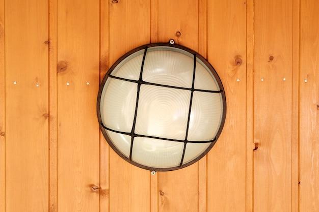 Een ronde lamp met een glazen kap en een gaashouder is aan het plafond geschroefd, omhuld met houten dakspaan en bedekt met gelige verf.