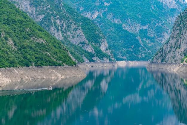 Een rondvaartboot met toeristen zwemt langs het schilderachtige meer tussen de kloof