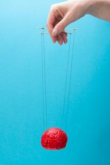 Een rood brein op een blauwe achtergrond, een hand die de geest manipuleert als een pop.