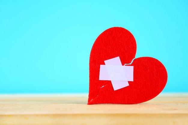 Een rood gevoeld hart dat in twee helften wordt gebroken, gelijmd door een pleister op een houten tafel op een blauwe ba