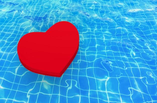 Een rood hart dat op de golvende achtergrond van de zwembadoppervlakte drijft.