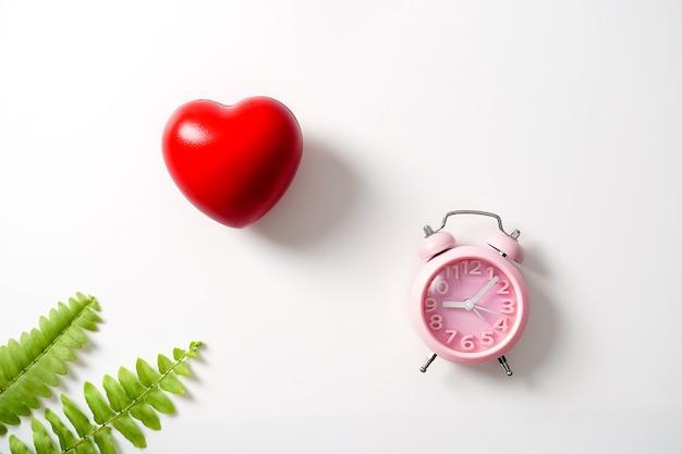 Een rood hart met een klok op een witte achtergrond valentijnsdag concept gezondheidszorg flat lay