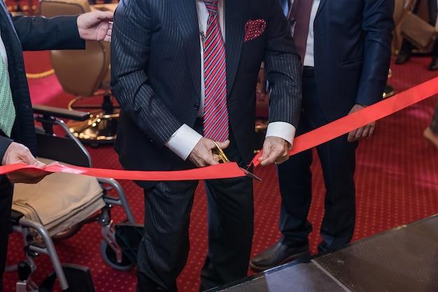 Een rood lint knippen met een schaar voor een nieuwe zakelijke onderneming of openingsceremonie