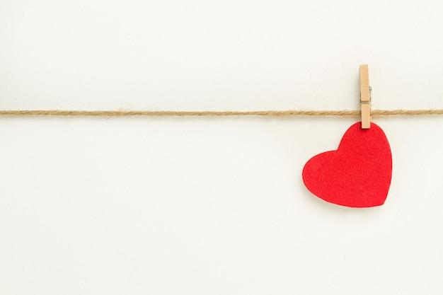 Een rood papier hart opknoping van een sisal garen op witte achtergrond
