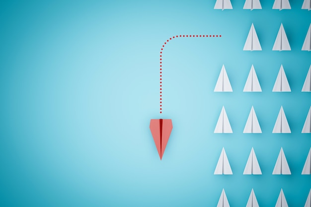 Een rood papieren vliegtuigje wijst op een andere manier op een blauwe achtergrond.