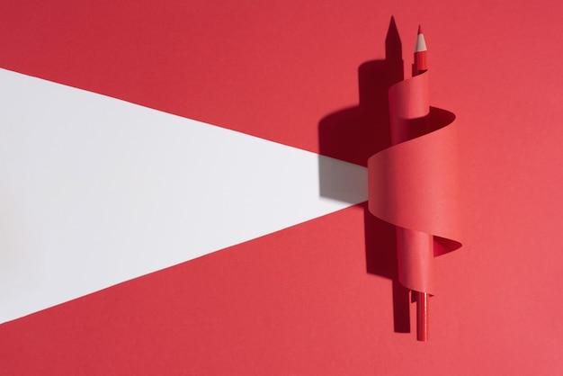 Een rood potlood in gekruld papier op rode achtergrond.