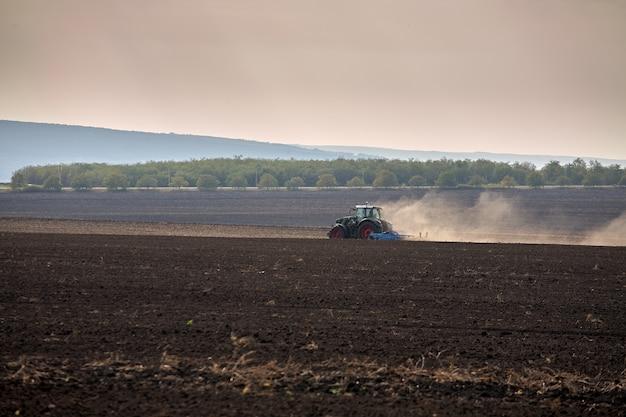 Een rood tractorgebied ploegen.