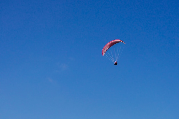 Een rood vliegtuig vliegt over de blauwe lucht