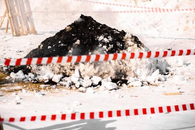 Een rood-witte signaalstrip verduistert het vuur, de kolen en de as