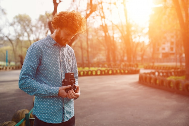 Een roodachtige gekrulde kerel die een middenformaat filmcamera in zijn handen houdt en foto's maakt op een zonnige dag