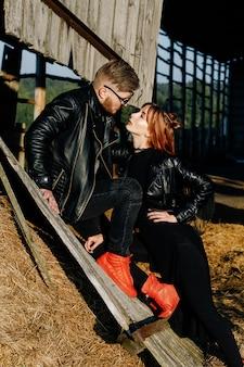 Een roodharig, dun meisje in zwarte kleding en rode schoenen kijkt naar de glitch van haar vriendje tegen de ruïnes