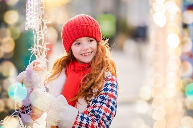 Een roodharig kindmeisje loopt en kijkt naar de kraam met slingers op de feestelijk versierde kerstmarkt in de stad.