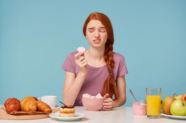 Een roodharig meisje dat tijdens het ontbijt aan een tafel zat, probeerde een marshmallow met fruit