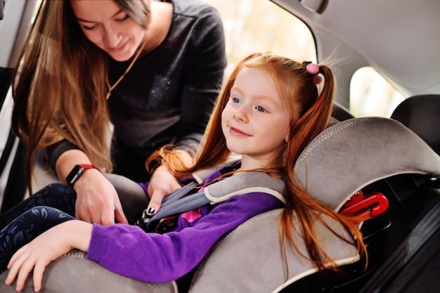 Een roodharig meisje glimlacht in de auto.
