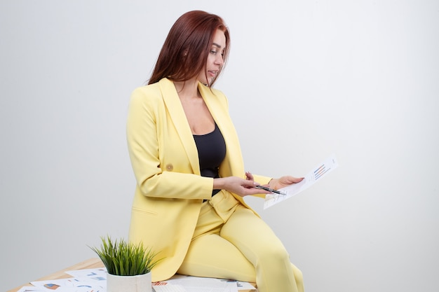 Een roodharig meisje in een geel pak zit op een stoel en leest documenten