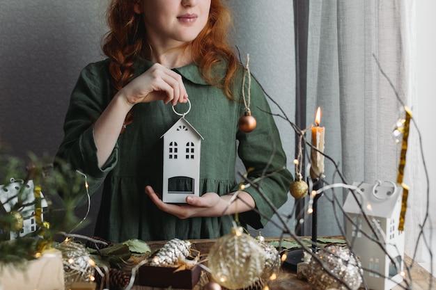 Een roodharig meisje in een groene linnen jurk kijkt naar kerstversieringen.