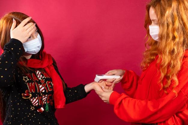 Een roodharig meisje in een medisch masker meet haar lichaamstemperatuur met een thermometer.