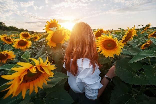 Een roodharig meisje in een veld met zonnebloemen kijkt naar de zonsondergang.