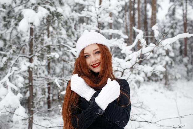 Een roodharig meisje met lang haar in een witte pet staat en glimlacht in een besneeuwd winterbos. groot portret van een roodharig meisje.