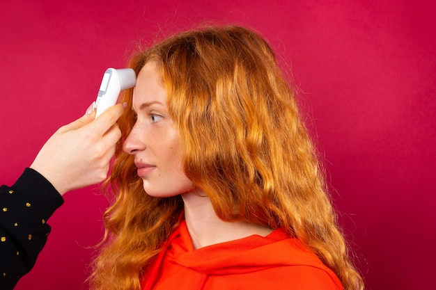 Een roodharig meisje wordt gemeten met een contactloze thermometer op haar voorhoofd. virus en pandemie concept.