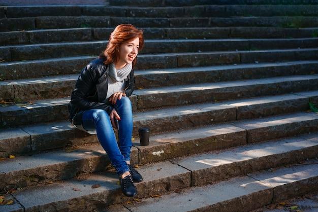 Een roodharige jonge vrouw in een leren jas en spijkerbroek zit op de trap met een kopje koffie en wordt wakker.
