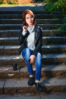 Een roodharige jonge vrouw in een leren jas en spijkerbroek zit op de trap met een kopje koffie