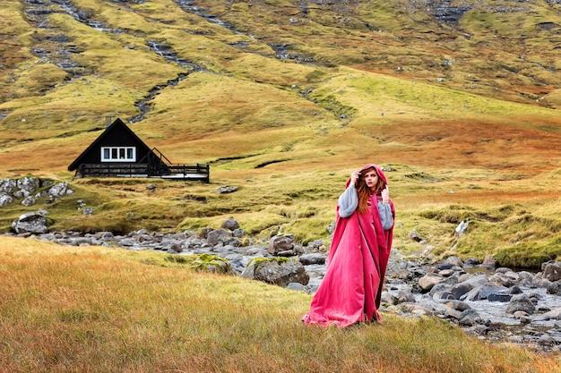 Een roodharige meisjeself in fantasievormige kleding blijft in de buurt van een beekje. faeröer