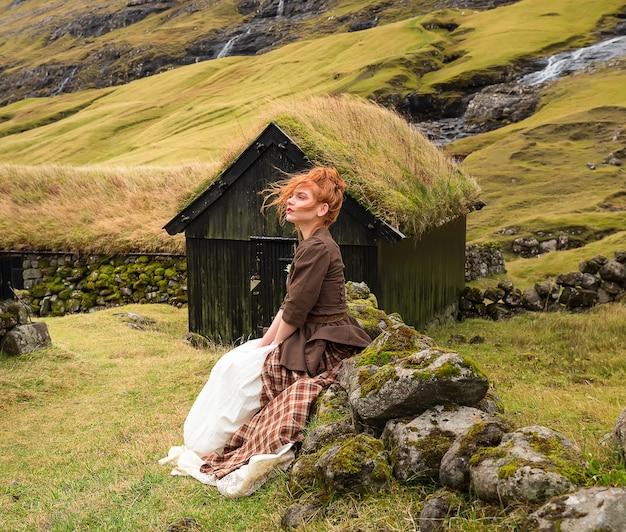 Een roodharige vrouw zittend op een stenen hek in ouderwetse kleren. saksun dorp, streymoy, faeröer