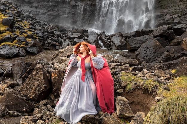Een roodharige vrouwelf in fantasievormige kleding blijft in de buurt van de fossawaterval. faeröer