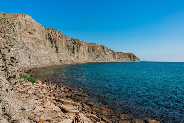 Een rotsachtig strand gemaakt van natuurlijke rechthoekige stenen op de krim een somber levenloos landschap