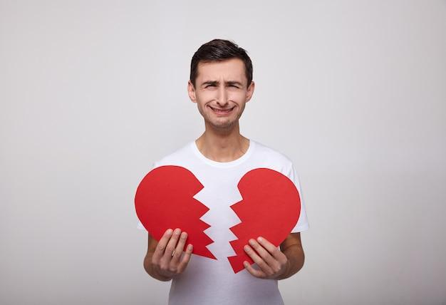 Een rouwende jongeman met een gebroken hart in zijn handen.