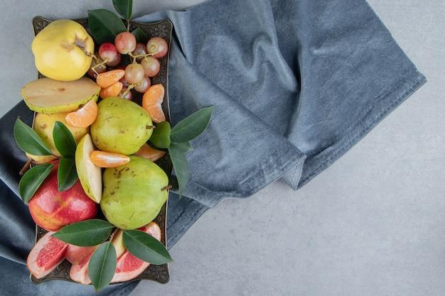 Een royale portie fruit op een dienblad op marmer
